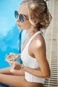 Mannequin blonde à la mode et sexy en maillot de bain blanc élégant et en lunettes de soleil à la mode, avec une coupe de champagne à la main, assise dans la piscine et posant en plein air