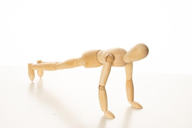 Mannequin en bois faisant des exercices de pompes