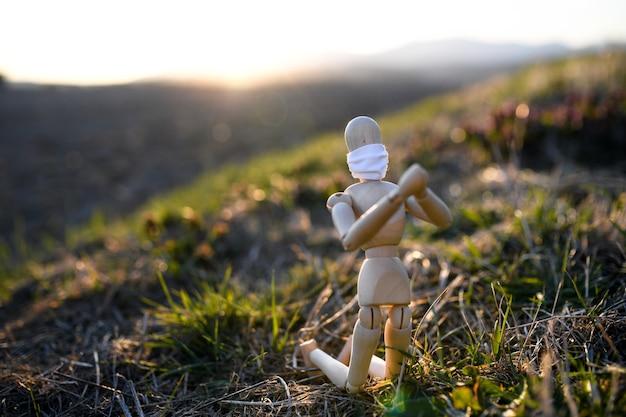 Mannequin en bois fatigué avec masque facial priant dans la nature, virus corona et concept de verrouillage.