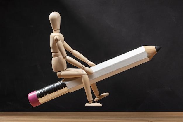 Mannequin en bois monté sur un crayon comme une fusée. retour au concept de l'école. espace copie