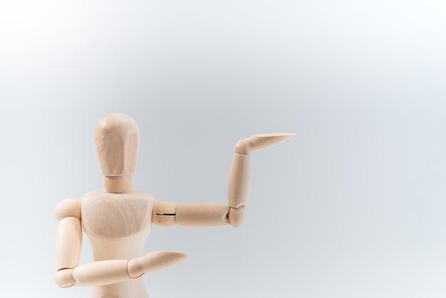Le mannequin en bois présente fièrement une chose invisible, un espace de copie isolé pour votre objet ou votre texte