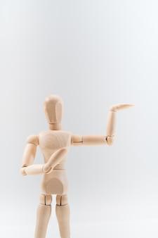 Le mannequin en bois présente fièrement quelque chose d'invisible, isolé