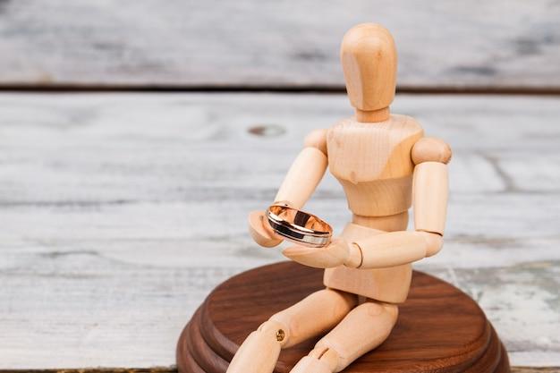 Mannequin en bois tient la bague de fiançailles.