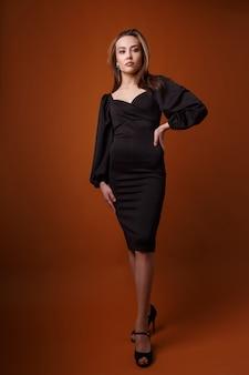 Mannequin élégant en robe noire avec décolleté profond, chaussures à talons hauts posant. asiatique maigre jeune femme se tient en robe de soirée sexy