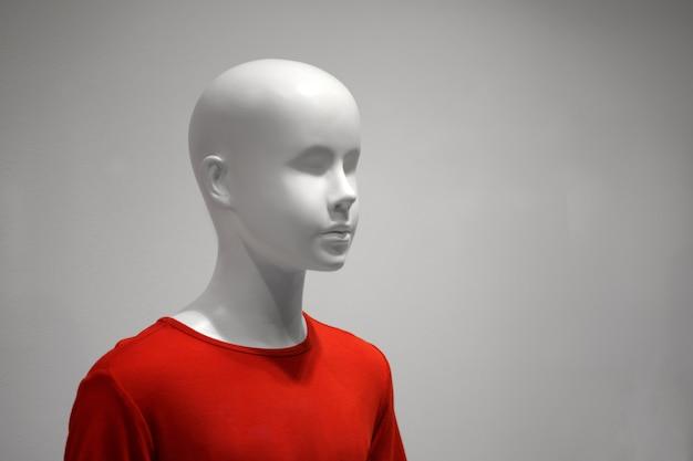 Un mannequin enfant blanc dans un t-shirt rouge