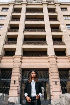 Mannequin femme afro-américaine. style de rue, grand immeuble, femme noire élégante, concept de beauté