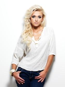 Mannequin femme aux longs cheveux blonds posant.
