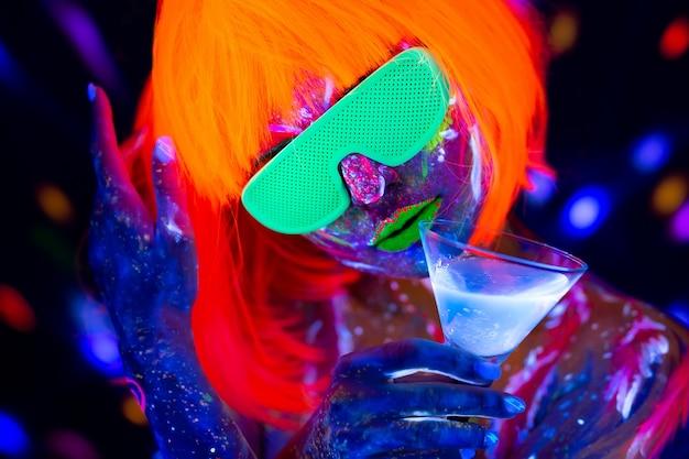 Mannequin femme buvant un cocktail alcoolisé en néon, discothèque. belle danseuse modèle fille colorée maquillage fluorescent lumineux