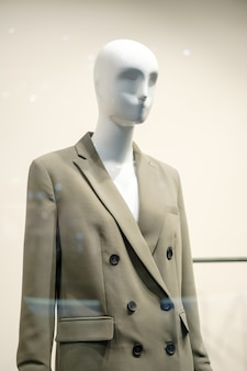 Mannequin femme dans une veste grise. voir à travers la fenêtre. concept de mode