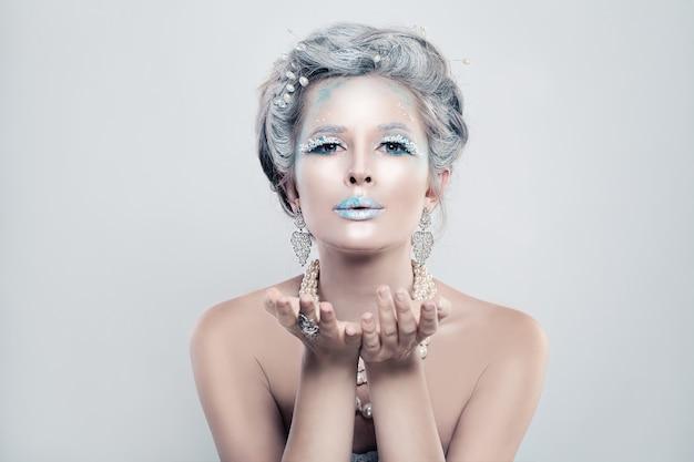 Mannequin femme hiver avec maquillage de paillettes de neige soufflant un baiser