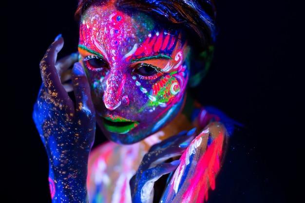 Mannequin femme en néon, portrait de belle fille modèle avec maquillage fluorescent, body art en uv, visage peint, maquillage coloré, sur fond noir
