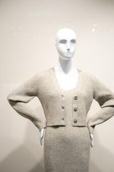 Mannequin femme vêtue d'une robe grise et d'une veste. voir à travers la fenêtre. concept de mode