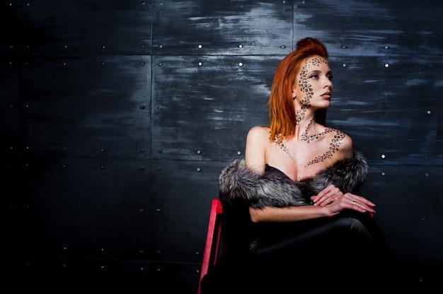 Mannequin fille aux cheveux rouge avec à l'origine maquillage comme prédateur léopard contre mur en acier. portrait en studio sur échelle.