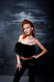 Mannequin fille aux cheveux rouge avec à l'origine maquillage comme prédateur léopard contre mur en acier.