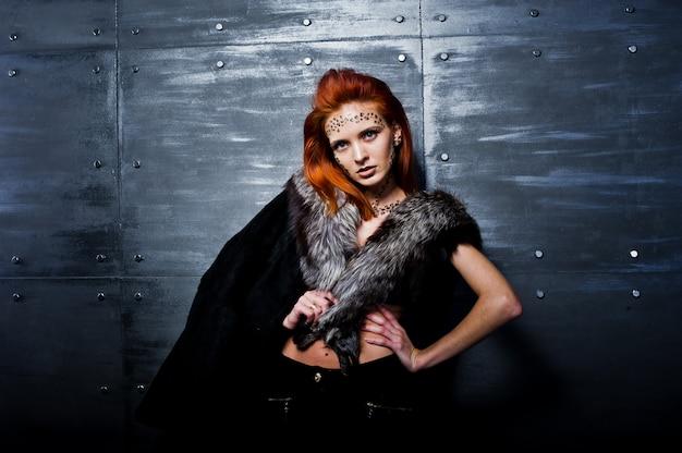 Mannequin fille aux cheveux rouge avec à l'origine maquillage comme l'usure de prédateur léopard sur les fourrures contre le mur en acier.