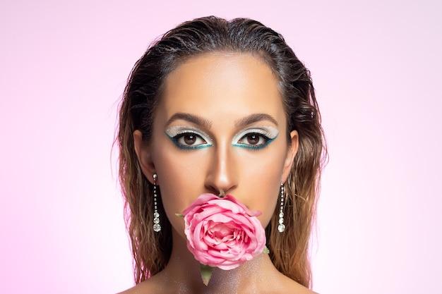 Mannequin avec fleur rose sur fond clair.