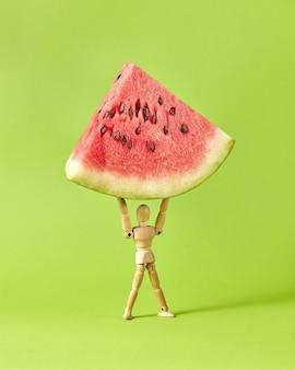 Mannequin humain en bois miniature détient la part de pastèque douce mûre fraîche