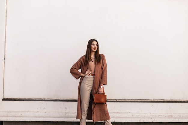 Mannequin de jeune femme européenne urbaine dans des vêtements marron élégants avec un sac à main en cuir posant près d'un bâtiment blanc vintage dans la rue. belle fille en tenue décontractée en ville. dame élégante.