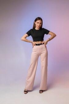 Mannequin jeune fille posant dans la lumière du studio néon pour la publicité du magasin de vêtements. concept de garde-robe élégant féminin. photo de haute qualité