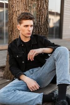 Mannequin jeune homme avec une coiffure élégante en veste noire en jean noir vintage