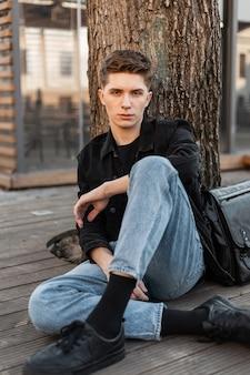 Mannequin jeune homme avec une coiffure en veste noire en jean noir vintage
