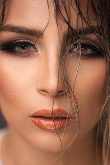Mannequin en maquillage de soirée avec des yeux enfumés et des tons bronzés