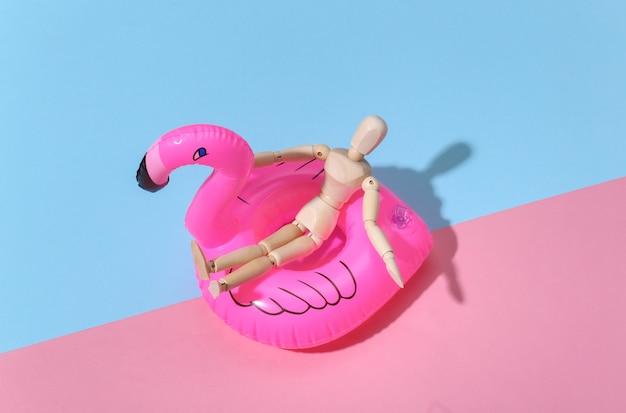 Mannequin marionnette avec flamant gonflable sur fond rose bleu vif. concept de vacances à la plage