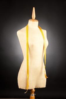 Mannequin sur mesure avec ruban à mesurer sur fond noir