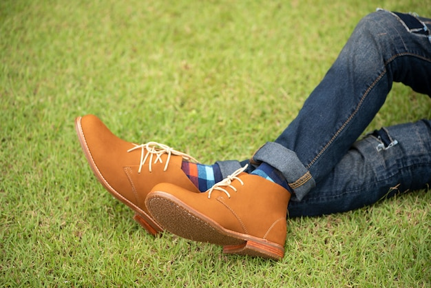 Mannequin portant des bottes en cuir marron et un jean assis sur l'herbe.