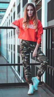 Mannequin portant un sweat à capuche rouge avec l'inscription los angeles posant dans la ville au parking tenue urbaine de mode style de vêtements de tous les jours