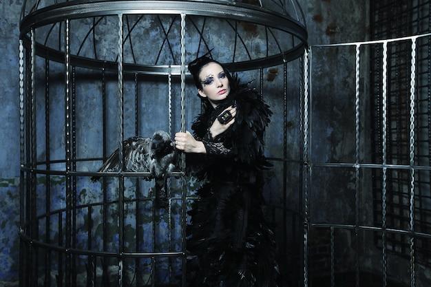 Mannequin en robe de fantaisie posant dans une cage en acier.