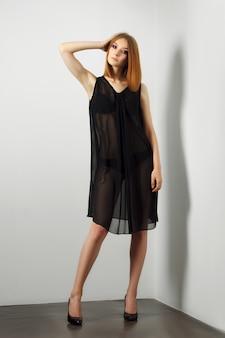 Mannequin sexy en lingerie noire et déshabillé transparent. jambes nues et talons hauts.