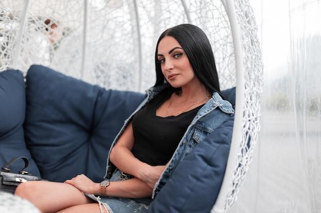 Mannequin tendance jeune femme séduisante dans des vêtements en jean à la mode avec de longs cheveux noirs se détend assis sur un fauteuil vintage sur la terrasse d'un café d'été dans la ville. belle fille à l'extérieur