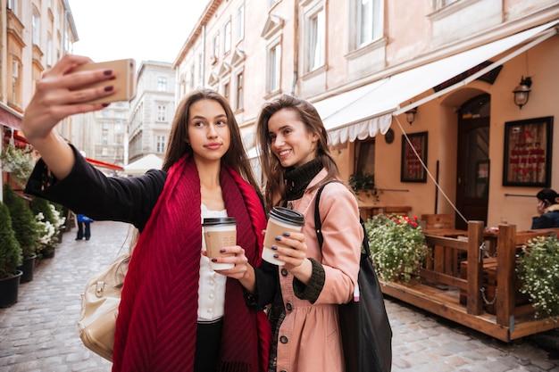 Des mannequins en manteaux font des selfies dans la rue. avec du café