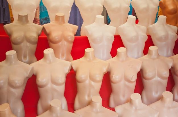 Mannequins en plastique nus blancs sur fond rouge.