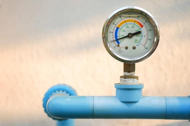 Manomètre d'eau sur tuyau de plomberie bleu avec arrière-plan flou naturel, espace de copie gratuit.
