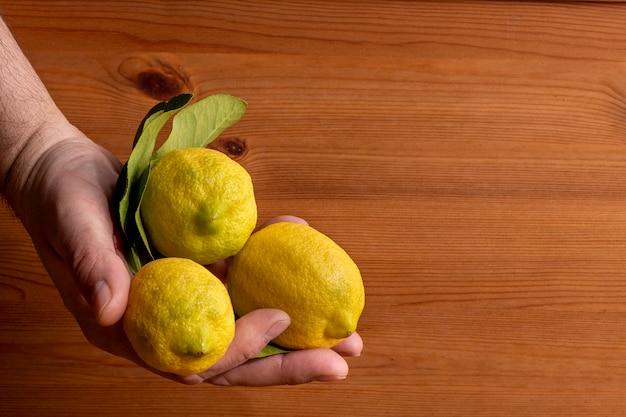 Manos con limones con fondo de madera.