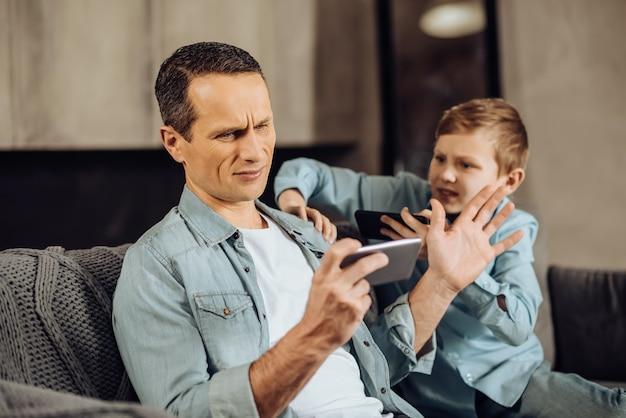 Manque d'attention. un pré-adolescent irrité serrant l'épaule de son père et essayant de le faire prêter attention à lui, tandis que l'homme essuie le garçon, étant trop occupé à jouer