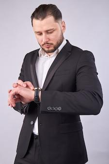 Mans looking at montre-bracelet isolé sur gris