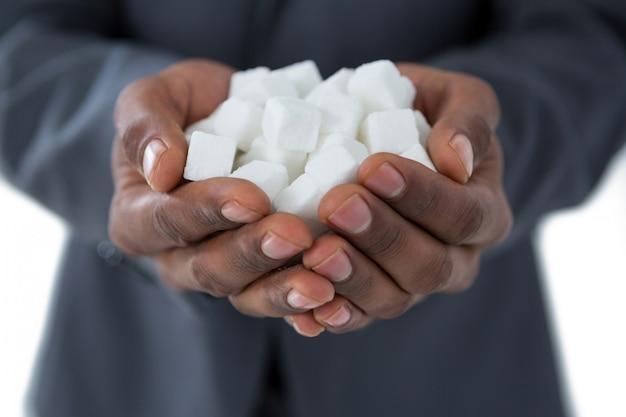 Mans main en coupe avec des cubes de sucre