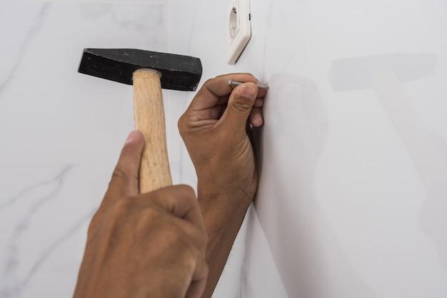 Mans mains martelant un clou dans un mur