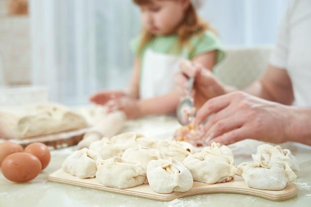 La manse alimentaire nationale ouzbek, comme des boulettes de pâte, met les ingrédients avec la main d'un homme. mise au point sélective