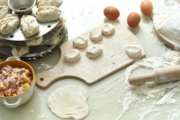 Manta alimentaire nationale ouzbek, comme des boulettes, fond d'ingrédients et produits semi-finis