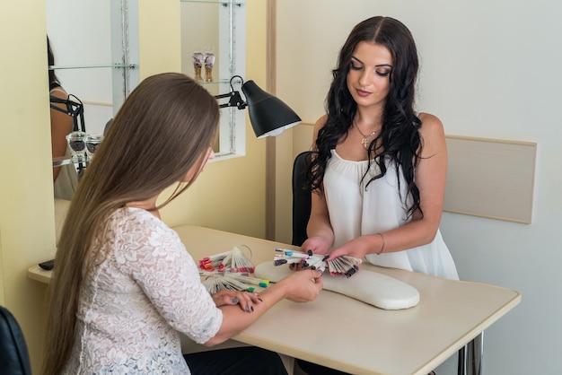 Manucure de belle femme montrant un échantillonneur de couleurs au client