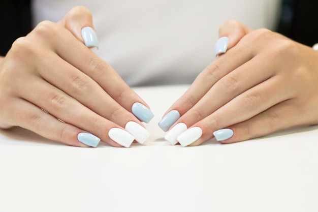 Manucure bicolore avec vernis à ongles bleu et blanc sur fond blanc