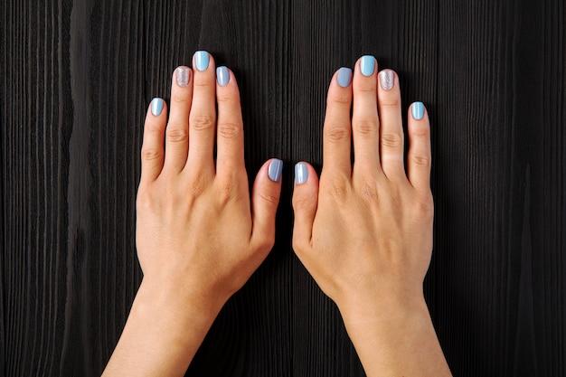 La manucure, bleue avec une couleur argentée, isolée sur un fond en bois noir