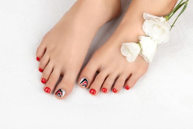 Manucure, concept de salon de beauté pédicure. pieds de femme sur fond gris