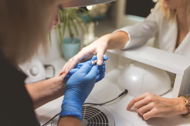 Manucure coupe la cuticule sur les ongles du client avec une pince