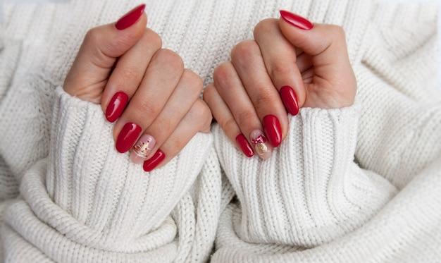 Manucure créative du nouvel an rouge avec un motif d'un arbre de noël et d'une cloche sur un fond de chandail