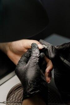 Manucure dans le salon. masters enlève le gel pour les ongles
